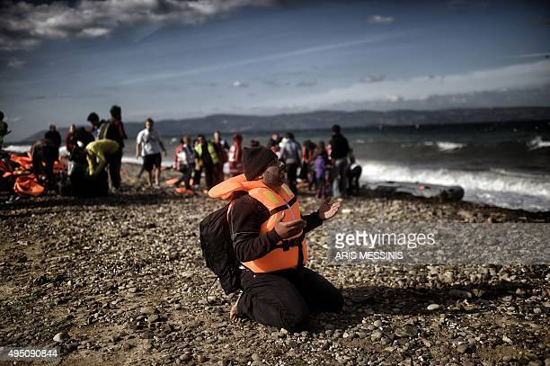 A man prays as refugees and migrants arrive on the Greek Lesbos island after crossing the Aegean Sea from Turkey on October 31 2015 AFP PHOTO / ARIS...