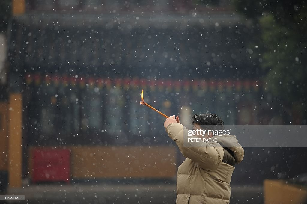 A man prays at a temple as it snows in Shanghai on February 7, 2013 ahead of the Lunar New Year. Preparations continue for the Lunar New Year which will celebrate the start of the Year of the Snake on February 10. AFP PHOTO / Peter PARKS