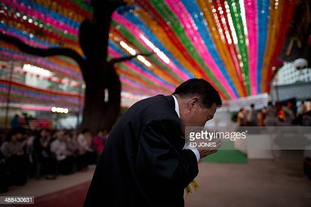 A man prays beneath lanterns during a ceremony marking Buddha's birthday at the Jogyesa temple in Seoul on May 6 2014 Buddha's birthday in South...