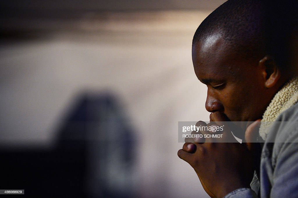 A man prays during a memorial ceremony for late South African former president Nelson Mandela at a local university in Mthata, on December 14, 2013. Nelson Mandela's remains were returned to his beloved rural childhood village ahead of a traditional burial on Sunday, the final leg of his exceptional 95-year journey. Mandela, the revered icon of the anti-apartheid struggle in South Africa and one of the towering political figures of the 20th century, died in Johannesburg on December 5 at age 95.