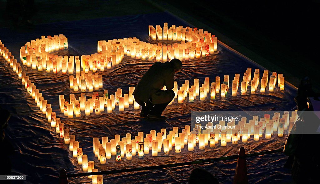 A man prays for the vectims at the numbers 311 lit by paper lanterns on the fourth anniversary of the Greaat East Japan Earthquake on March 11 2015...