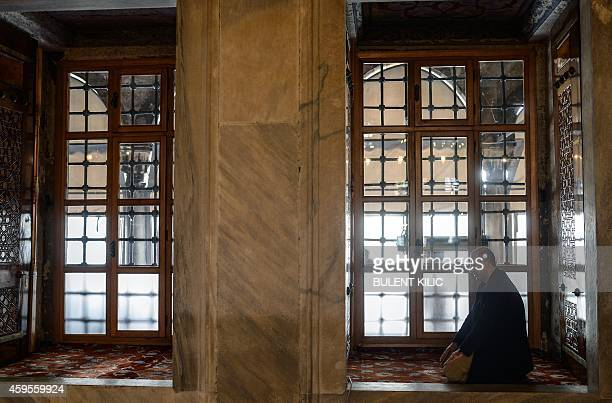 A man prays inside the Blue Mosque in Istanbul on November 25 2014 Pope Francis will visit Turkey on November 2830 eight years after his predecessor...