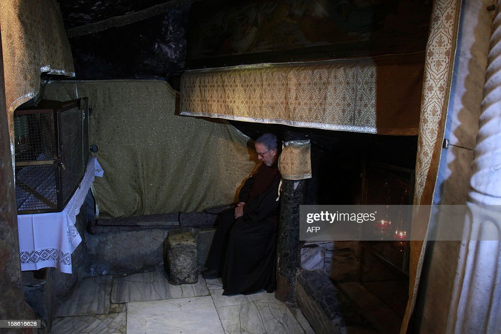 A man prays inside the Grotto where Christians believe the Virgin Mary gave birth to Jesus Christ in the Church of the Nativity, in the West Bank biblical town of Bethlehem, the traditional birthplace of Jesus as preparations for Christmas celebrations get underway on December 21, 2012.