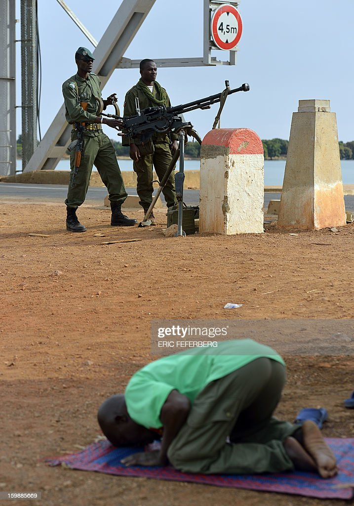 A man prays near Malian soldiers controlling a strategic bridge on the Niger river on January 22, 2013 near Markala, 270km North of Bamako. Mali's army chief today said his French-backed forces could reclaim the northern towns of Gao and fabled Timbuktu from Islamists in a month, as the United States began airlifting French troops to Mali.