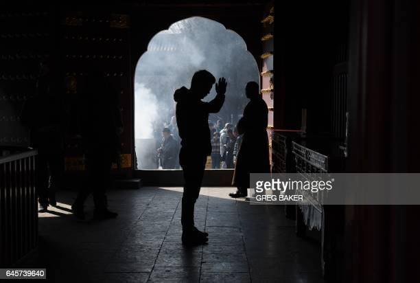 A man prays on the first day of the Tibetan New Year at the Yonghegong Lama Temple in Beijing on February 27 2017 Tibetan New Year known as Losar is...