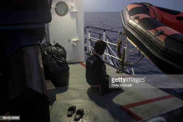 A man prays onboard the Migrant Offshore Aid Station Phoenix vessel enroute to Italy on June 11 2017 off Catania Italy An estimated 230000 refugees...