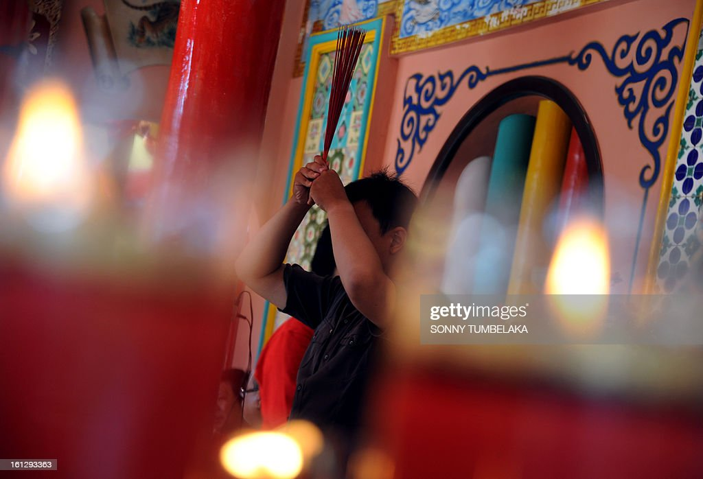 A man prays to celebrate the Chinese Lunar New Year at a Dharmayana temple in Kuta on Indonesia's resort island of Bali on January 10, 2013. Lunar New Year is celebrated in many parts of the predominantly Islamic country of 240 million people where Chinese heritage took roots through ancient transmigration. AFP PHOTO / Sonny TUMBELAKA