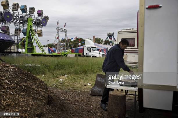 A man prepares a meal near carnival rides in the parking lot of the Neshaminy Mall in Bensalem Pennsylvania US on Saturday May 20 2017 As mall owners...