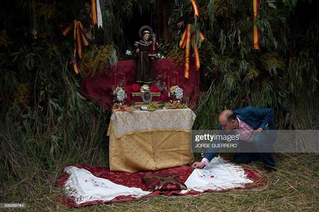 A man prepares an altar before the procession during the Corpus Christi celebrations in El Gastor, southern Spain on May 29, 2016. The village of El Gastor celebrate the feast of Corpus Christi (or Body of Christ in Latin) covering the streets and facades of houses with branches of trees and grass. / AFP / JORGE