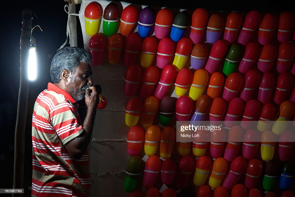 A man prepares balloons for a game at the Marina Beach on February 24, 2013 in Chennai, India. Marina Beach is an urban beach along the Bay of Bengal, which is part of the Indian Ocean. The beach runs a distance of 13km (8.1 miles), making it the longest natural urban beach in the country and the world's second longest.