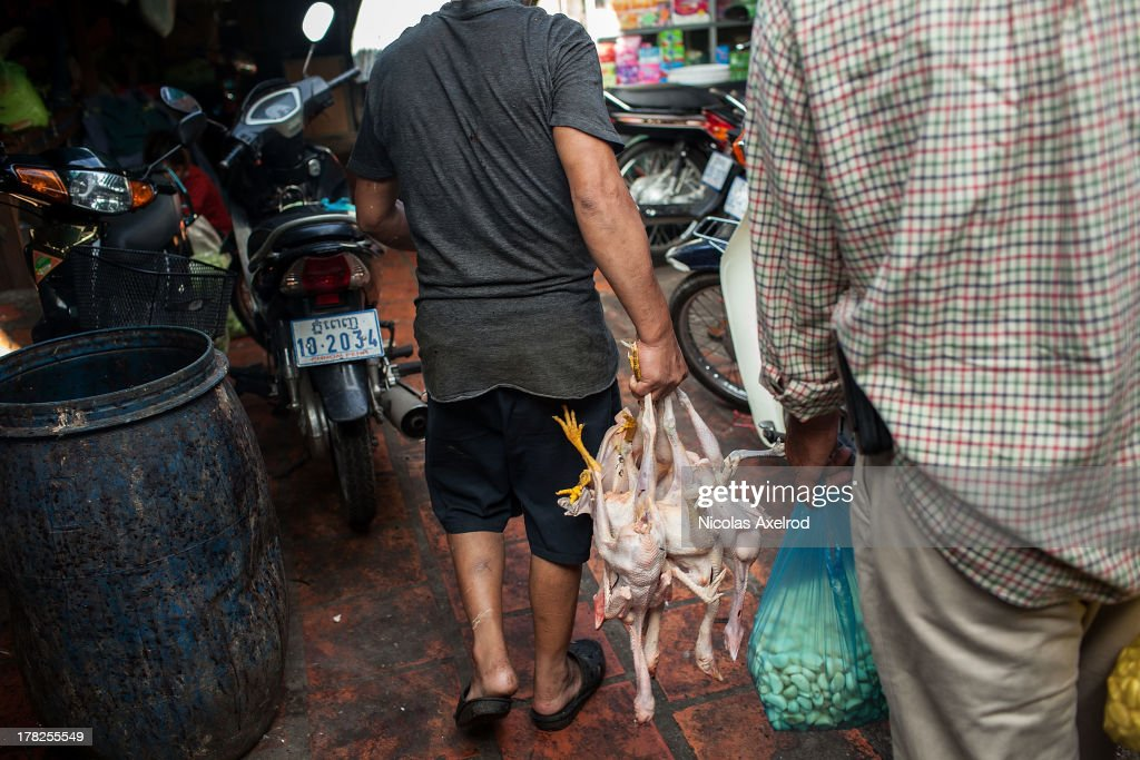 A man prepares chickens for sale at the Kandal Market in central Phnom Penh on August 25, 2013 in Phnom Penh, Cambodia. Cambodia has seen the worst out break of Avian influenza H5N1 since the disease was first identified, so far this year 17 cases have been report, 10 of which have been fatal.