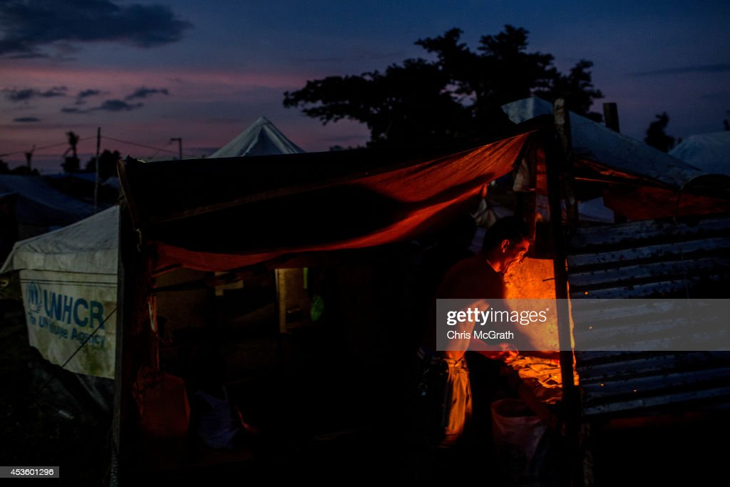 A man prepares dinner over a fire at an evacuation center on August 14, 2014 in Tanauan, Leyte, Philippines. Many of the families living in this camp have been there since the typhoon hit last November, they have planted vegetable gardens and house pigs and chickens. The tents which are made to last only six months are worn through with holes and leak water. Residents of Tacloban city and the surrounding areas continue to focus on rebuilding their lives nine months after Typhoon Haiyan struck the coast on November 8, 2013, leaving more than 6000 dead and many more homeless. With many businesses and government operations back up and running and with the recent start of the years typhoon season, permanent housing continues to be the main focus with many families still living in temporary accommodation. As well as continuing recovery efforts Leyte is preparing for the arrival of Pope Francis, who will visit the region from January 15- 19.
