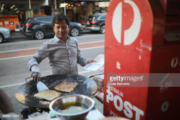 A man prepares food in a makeshift streetfood stall on Haldon Street in the southwestern suburb of Lakemba on May 27 2017 in Sydney Australia Muslims...