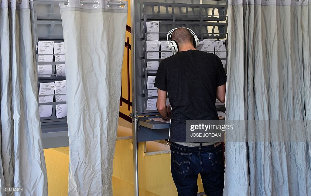 A man prepares his ballot in a polling booth before voting in Spains general election at the Bernadette college polling station in Moncloa-Aravaca, Madrid, on June 26, 2016. Spain votes today, six months after an inconclusive election which saw parties unable to agree on a coalition government. JORDAN