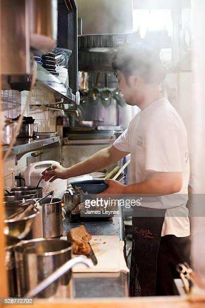 A man prepares ramen noodle soup at a restaurant in Tokyo