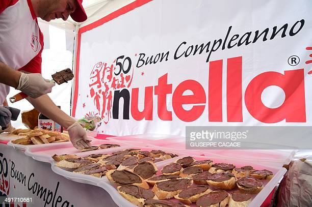 A man prepares tartines of Nutella on May 17 2014 in Alba northern Italy during the celebrations of the 50th anniversary of Nutella the chocolate...