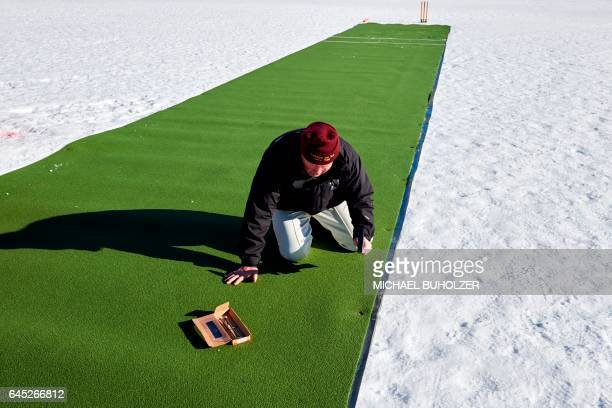 A man prepares the pitch ahead of the 30th Cricket on Ice tournament held on the frozen surface of the Lake St Moritz on February 25 2017 The...