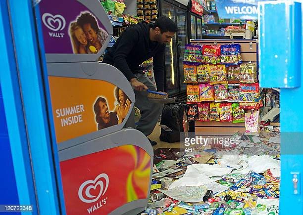 A man prepares to clean up the remains of his looted shop in Croydon south of London on August 9 following a third night of violence on the streets...