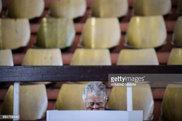 TOPSHOT A man prepares to fill out his ballot paper at the polling station in Pristina on June 11 2017 during early parliamentary elections in Kosovo...