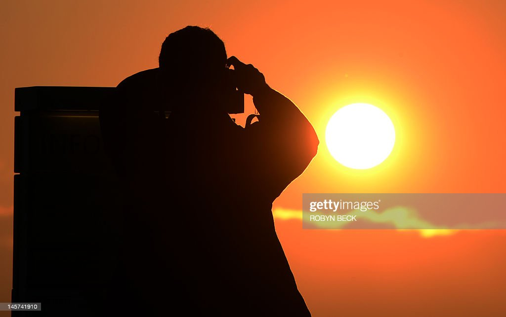A man prepares to press the shutter on his camera as he takes a picture of the sunset from The Griffith Observatory in Los Angeles, California June 4, 2012. June 5 will be the first time since 1882 that the Transit of Venus in front of the sun will be seen in the western United States. Since the telescope's invention the Transit of Venus has only been viewable anywhere in the world in the years 1631, 1639, 1761, 1769, 1874, 1882 and 2004, according to NASA's Fred Espenak.