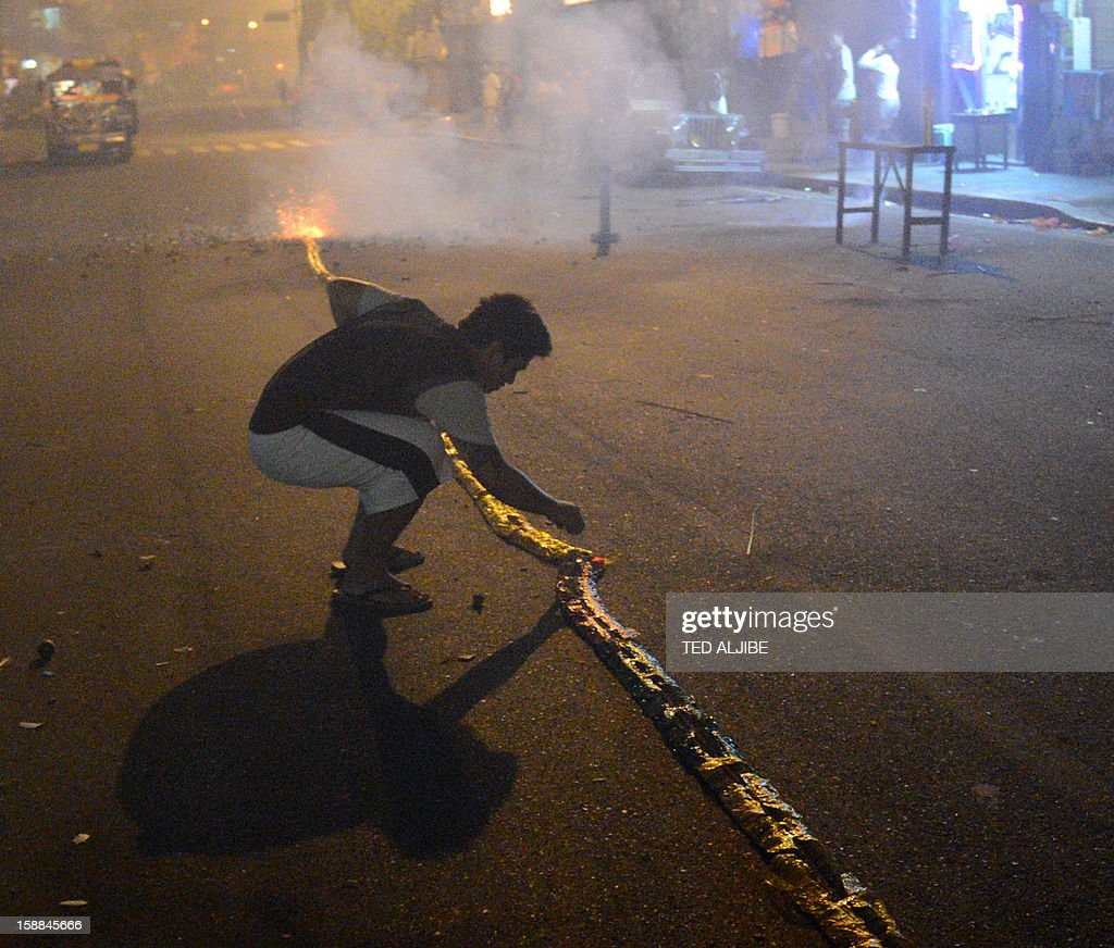 A man prepares to set off firecrackers to usher in New Year's Day in Manila early on January 1, 2013. In the capital Manila, authorities had been bracing for the annual rush of injuries as families celebrated with do-it-yourself firework displays and shot celebratory bullets into the air.
