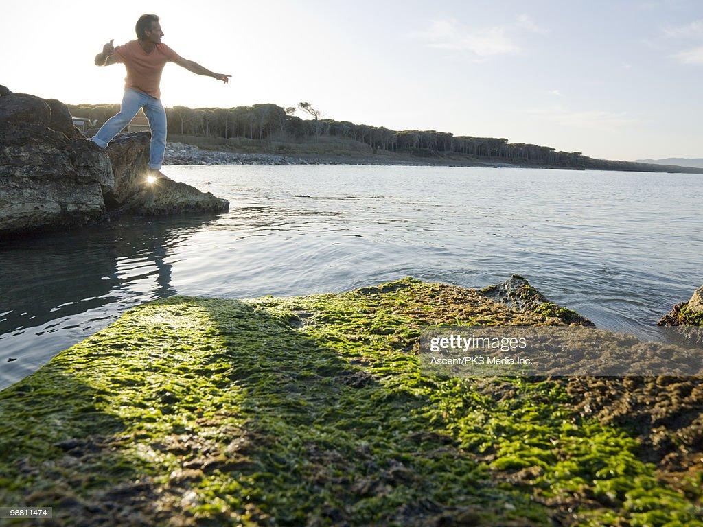 Man prepares to skip stone across calm sea surface : Stock Photo