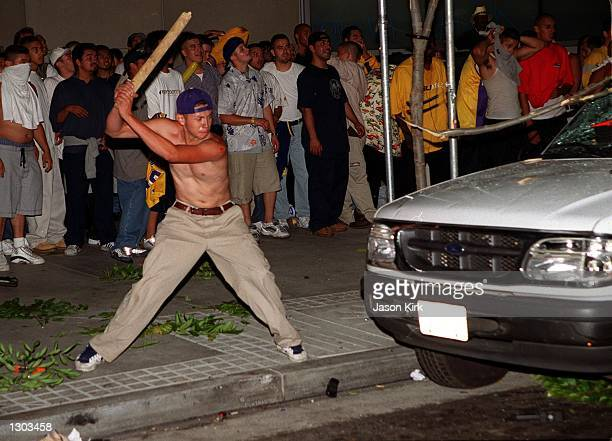 A man prepares to smash a car as rioting breaks out after the Los Angeles Lakers'' victory in the NBA Finals June 19 2000 in Los Angeles CA...