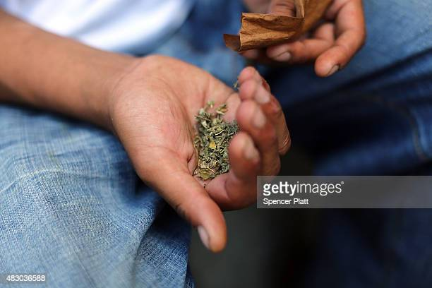 A man prepares to smoke K2 or 'Spice' a synthetic marijuana drug along a street in East Harlem on August 5 2015 in New York City New York along with...