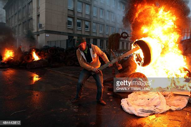 A man prepares to throw an burning tire as farmers protest in front of the prefecture early on August 19 2015 in SaintLo northwestern France AFP...