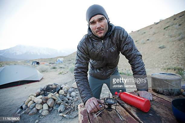 A man preparing a camp meal.