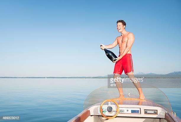 Mann, die Vorbereitung einer Champagner-Dusche auf einem Boot