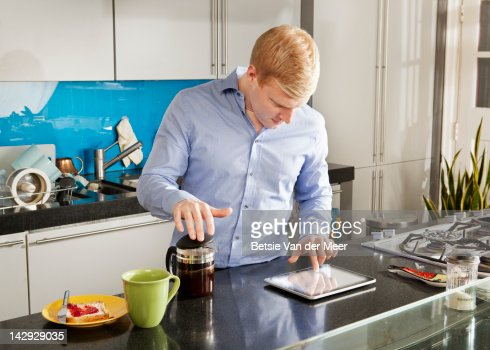 man preparing coffee while looking at i pad. : Stock Photo