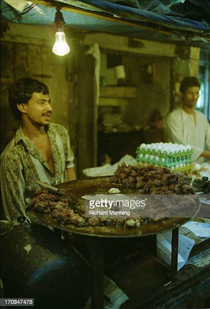 Man preparing food during the night time feast that follows the days fast during Ramadan at the Bindi Bazaar in Mumbai India January 1997