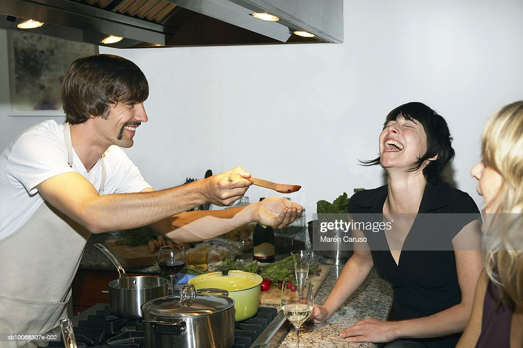 Man preparing food for female friends in kitchen