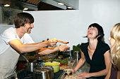 Man preparing food for female friends in kitchen