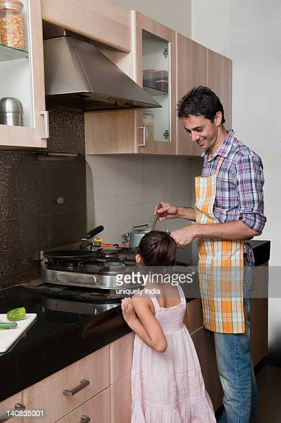 Man preparing food in the kitchen with his daughter
