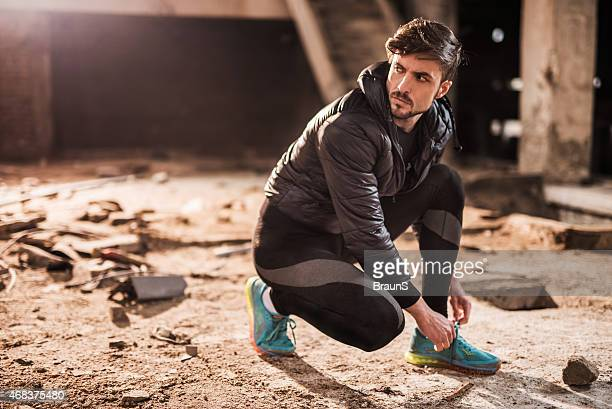 Man preparing for exercising in ruin and tying his shoelaces.