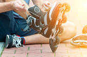 Man preparing for roller blading, putting on rollerblades.