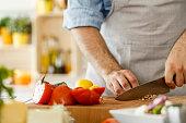 Man preparing healthy vegetables salad, cutting almond