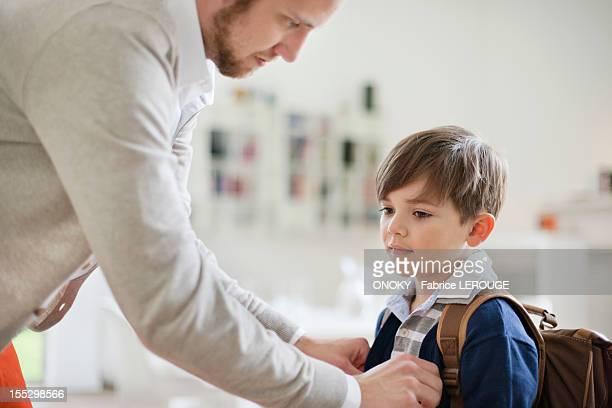 Man preparing his son for school