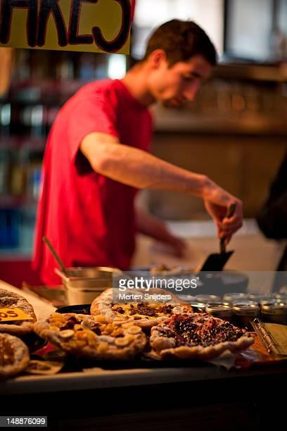 Man preparing Hungarian bread dishes at Vasarcsarnok Market.
