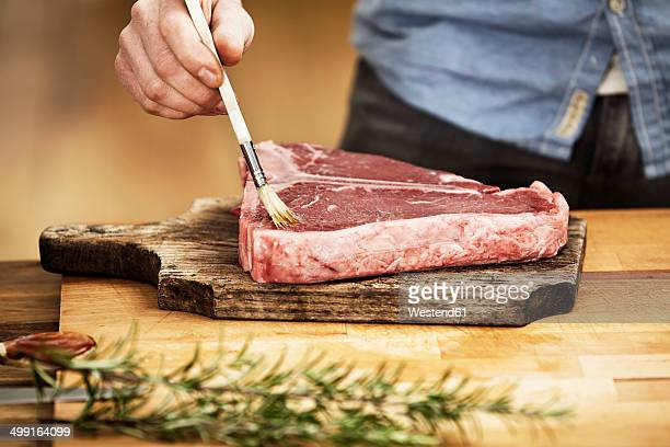 Man preparing steak in kitchen