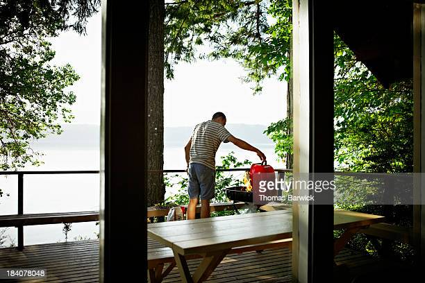 Man preparing to cook on barbecue on deck of cabin