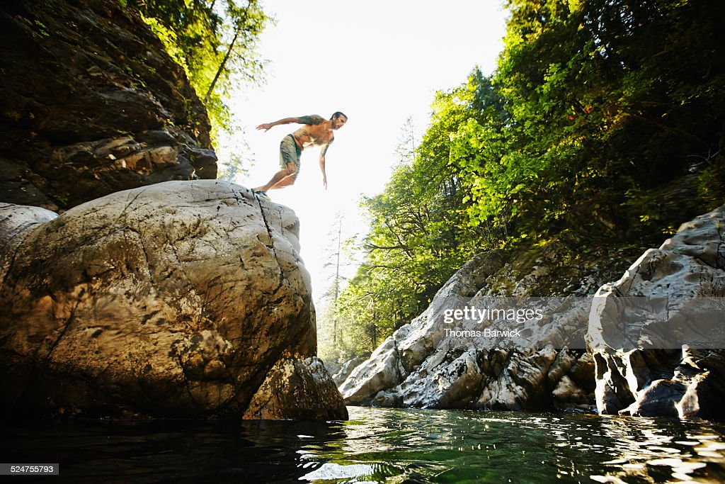 Man preparing to dive off of boulder into river : Stock Photo