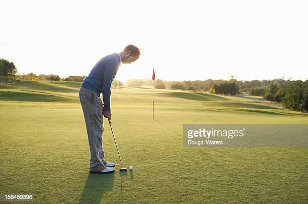 Man preparing to putt golf ball on green.
