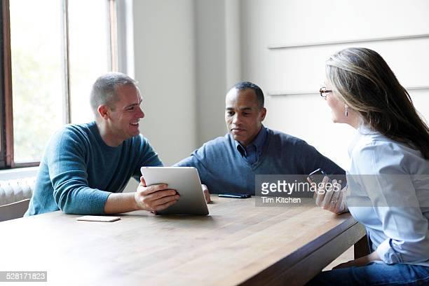 Man presenting digital tablet in meeting at table