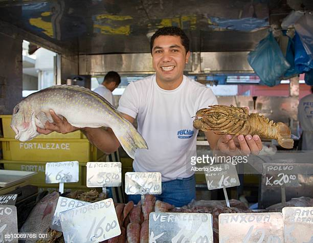 Man presenting fish at outdoor market