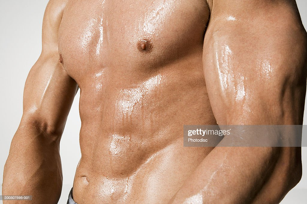 Man presenting muscles, mid section : Stock-Foto