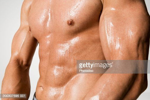Man presenting muscles, mid section : Stock Photo