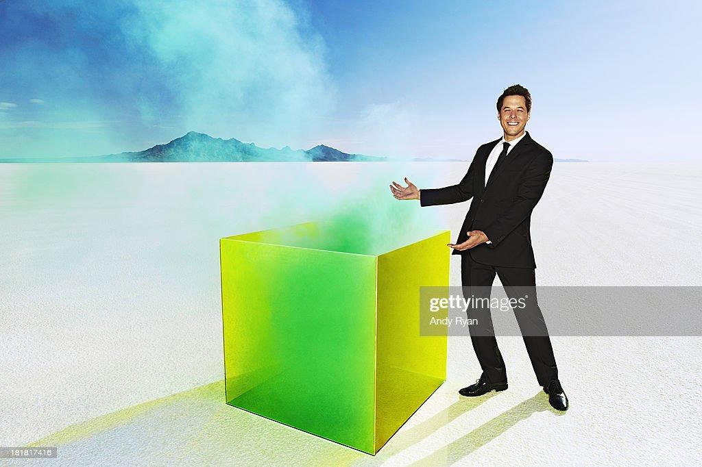 Man presenting smoking box in desert.